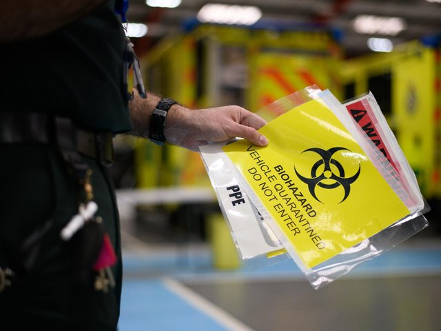 A paramedic holds a sign warning crew members not to enter a contaminated vehicle. Photo: PA