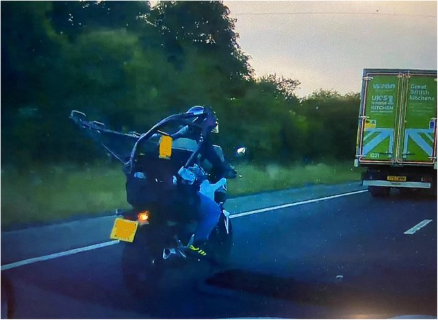 The biker was spotted travelling on the M18 with a motorbike framed strapped to his back.
