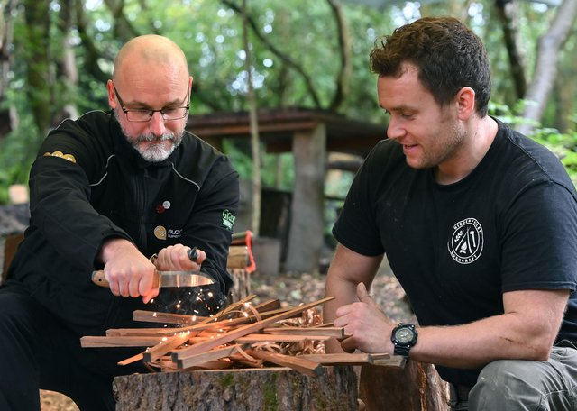 Nathan Pritchard (Flooring Superstore) lighting a campfire under the guidance of Nick Goldsmith, who runs Hidden Valley Bushcraft
