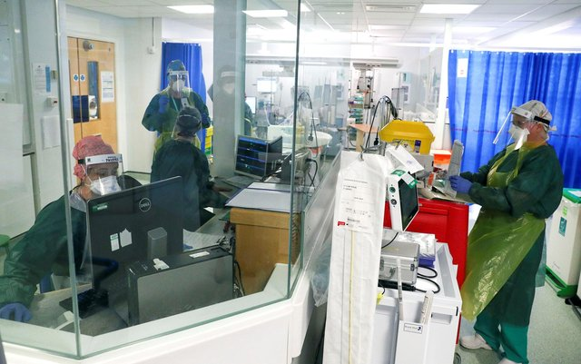 """Medical staff wearing full PPE (personal protective equipment), including a face mask, long aprons, and gloves as a precautionary measure against COVID-19, work on an Intensive Care Unit (ICU) ward treating patients with COVID-19, at Frimley Park Hospital in Frimley, southwest England on May 22, 2020. - Britain's number of deaths """"involving"""" the coronavirus has risen to 46,000, substantially higher than the 36,914 fatalities officially reported so far, according to a statistical update released Tuesday. (Photo by Steve Parsons / POOL / AFP) (Photo by STEVE PARSONS/POOL/AFP via Getty Images)"""