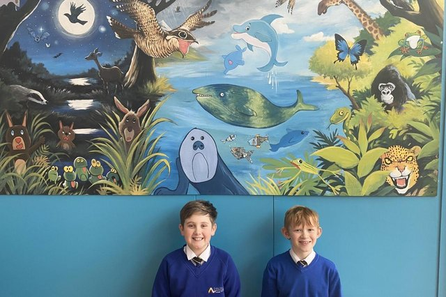 Archie and Chase with the nightjar mural at Hatfield Woodhouse Primary School.