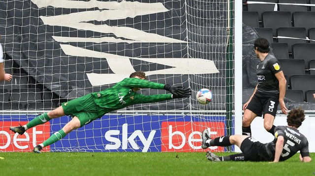 Louis Jones makes an excellent save from MK Dons' Will Grigg. Picture: Howard Roe/AHPIX