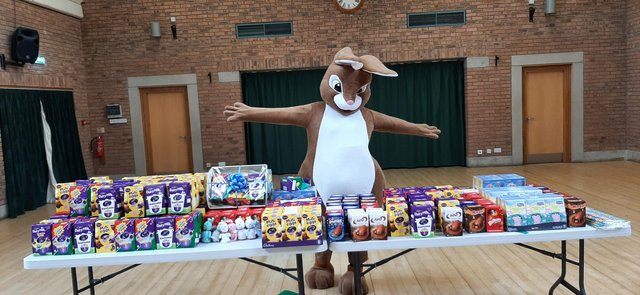A group of volunteers is collecting Easter eggs for children.