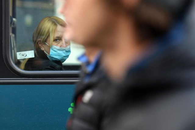 A woman wearing a protective face covering to combat the spread of the coronavirus looks from the window of a bus