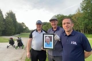 John and his brothers with a photo of their dad