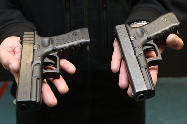 One of these Glock 17 pistols is a Police issue side arm the other is a plastic BB gun and even the officers cannot tell them apart without handling them