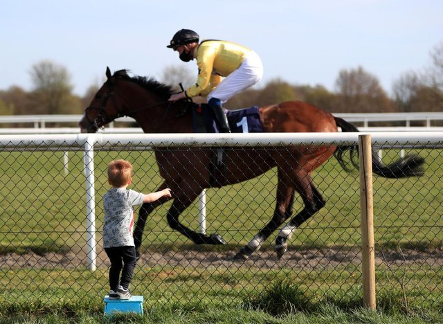 A young spectator watches Sam James riding Rum Runner go past in the Sky Sports Racing Virgin 535 Handicap at Doncaster Racecourse on April 23. Photo: Mike Egerton - Pool / Getty Images