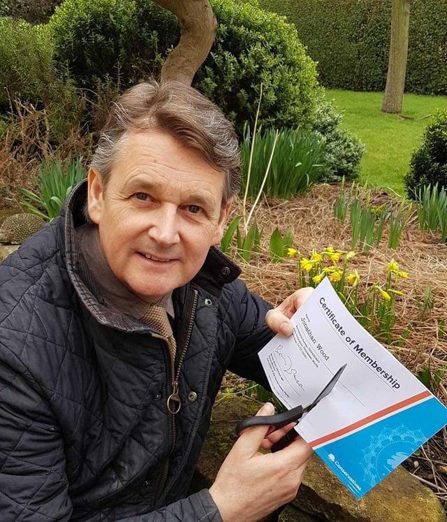Councillor Jonathan Wood cuts up his Conservative Party membership
