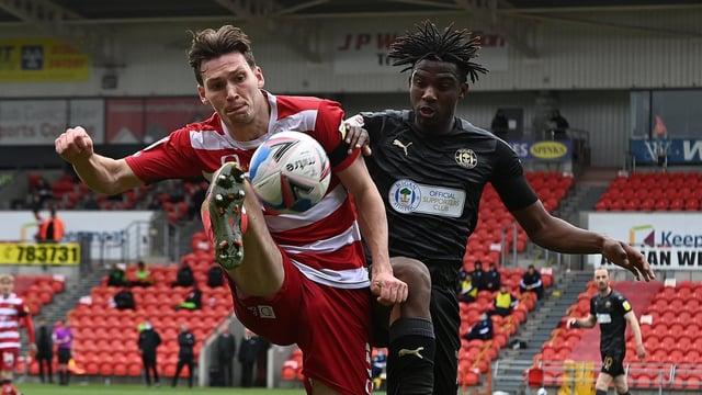 Joe Wright battles with Wigan goalscorer Viv Solomon-Otabor. Picture: Andrew Roe/AHPIX