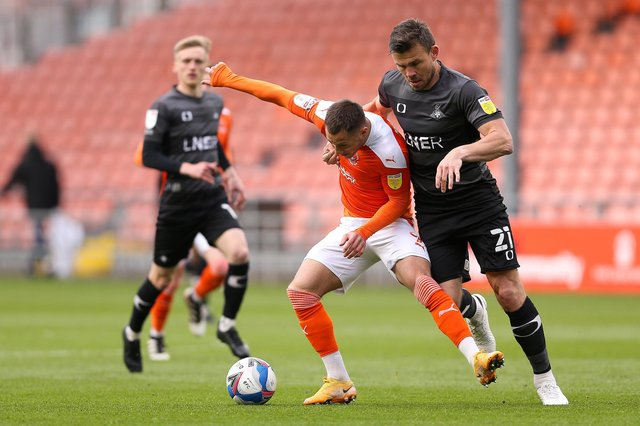 Doncaster Rovers player-manager Andy Butler battles with Blackpool's Jerry Yates.