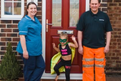 Keyworker parents with their daughter dressed as a super hero.